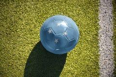 Fotbollbollen med nationsflaggan av Federated States of Micronesia ligger på fältet arkivfoto