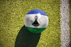 Fotbollbollen med nationsflaggan av Lesotho ligger på fältet Royaltyfri Fotografi