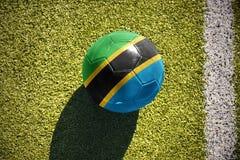 Fotbollbollen med nationsflaggan av Tanzania ligger på fältet Arkivfoto