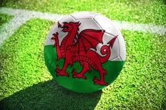 Fotbollbollen med nationsflaggan av Wales ligger på det gröna fältet Arkivbild