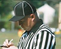 Fotbolldomare som gör anmärkningar under en lek royaltyfria bilder