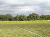 Fotbollfält i fält av träd Arkivfoton