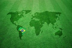 Fotbollfält med den Brasilien flaggavärldskartan Arkivfoto