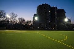 Fotbollfält och flerfamiljshus på natten, New York City Arkivbilder