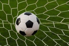 Fotbollfotboll i mål förtjänar med fältet för grönt gräs Fotografering för Bildbyråer