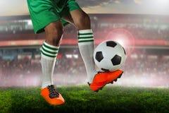 Fotbollfotbollsspelare i sportstadionfält mot fanklubban Royaltyfri Fotografi