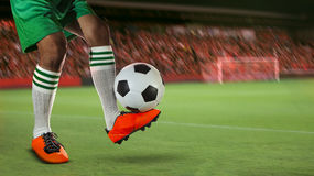 Fotbollfotbollsspelare i sportstadionfält mot fanklubban Royaltyfri Bild