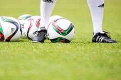 Fotbollinstruktör med fotbollbollar runt om honom Royaltyfria Bilder