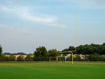 Fotbollmålstolpe på ett högstadiumfält i aftonsolen royaltyfri fotografi