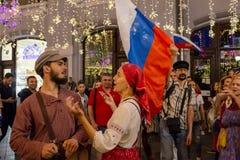 Fotbollsfan av olika länder firar segern av det ryska laget över Spanien dansa som är traditionellt Arkivbilder
