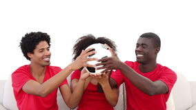 Fotbollsfan i rött sammanträde på soffainnehav klumpa ihop sig lager videofilmer