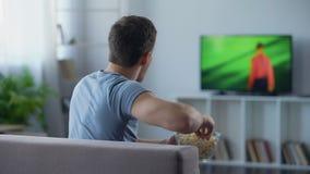 Fotbollsfan som äter popcorn och att kritisera spelare på tv som undervisar hur man gör poäng stock video