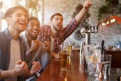 Fotbollsfan som håller ögonen på matchen i stång och dricker öl fotografering för bildbyråer