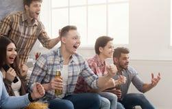 Fotbollsfan som hemma håller ögonen på fotboll på tv arkivfoton