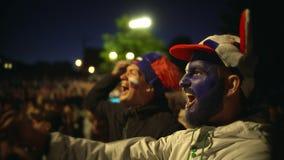 Fotbollsfanskriet jublar det favorit- laget för målet som hoppar vänbakgrundsfolkmassan arkivfilmer