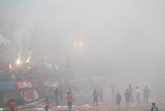Fotbollsmatch som stoppas på grund av rök från fyrverkerier Royaltyfri Foto