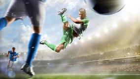 Fotbollspelare i handling på för stadionbakgrund för dag den storslagna panoraman royaltyfri fotografi