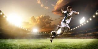 Fotbollspelare i handling på bakgrund för solnedgångstadionpanorama Arkivbild