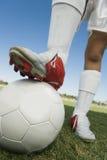 Fotbollspelare med benet på boll arkivbild