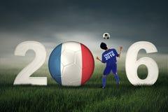 Fotbollspelare med bollen och nummer 2016 Arkivbild