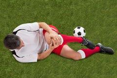 Fotbollspelare med skada i knä arkivbild