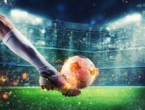 Fotbollspelare med soccerball på brand på stadion under matchen Arkivbild