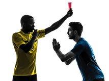 Fotbollspelare och domare för två män som visar konturn för rött kort Royaltyfria Foton