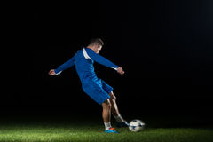 Fotbollspelare som gör spark med bollen Royaltyfri Fotografi