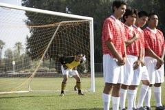 Fotbollspelare som i rad står förbereda sig för frispark Arkivbild