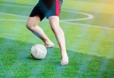 Fotbollspelare som inte bär en sportskjorta och gör barfota, hastighetskörning för att skjuta bollen till målet på grön konstgjor royaltyfri foto