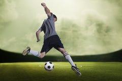 Fotbollspelare som sparkar bollen i en stadion, grön himmel med moln Arkivfoto