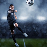 Fotbollspelare som sparkar bollen i en stor stadion Arkivbilder