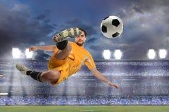 Fotbollspelare som sparkar bollen i Midair royaltyfria bilder