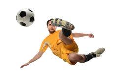Fotbollspelare som sparkar bollen i Midair royaltyfri bild