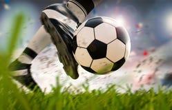 Fotbollspelare som sparkar fotbollbollen i rörelse Arkivfoto
