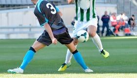 Fotbollspelare som spelar bollen Fotografering för Bildbyråer