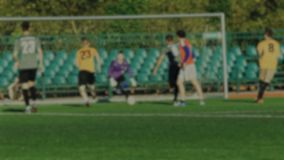 Fotbollspelaren anfaller, och målvakten fångar en boll, fotbollleken som är suddig för bakgrund arkivfilmer