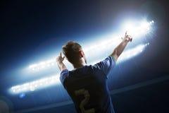 Fotbollspelaren med armar lyftte bifallet, stadion på nattetid Arkivbild