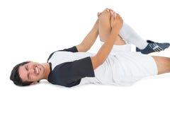 Fotbollspelaren som ner ligger och in ropar, smärtar Fotografering för Bildbyråer