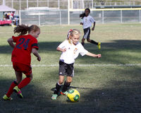 Fotbollsspelare för flickaungdomfotboll som kör för bollen Royaltyfri Fotografi