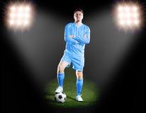 Fotbollsspelare i blå likformig på gräsfält i strålkastaren Fotografering för Bildbyråer
