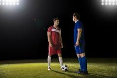 Fotbollsspelare i en övre position för utmaning royaltyfri bild