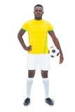 Fotbollsspelare i gult anseende med bollen Royaltyfria Foton