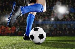 Fotbollsspelare i handlingspring och dregla på fotbollstadion som spelar matchen