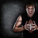 Fotbollsspelare som är aggressiv med amerikansk fotboll Royaltyfri Bild