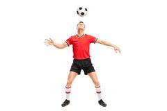Fotbollsspelare som jonglerar en boll på hans huvud Fotografering för Bildbyråer