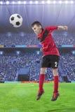 Fotbollsspelare som slår bollen med huvudet på en fotbollstadion arkivbild