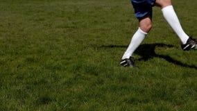 Fotbollsspelare som sparkar bollen på gräs lager videofilmer