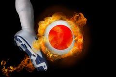 Fotbollsspelare som sparkar flamma den Japan bollen Royaltyfri Foto