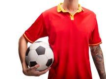 Fotbollsspelareanseende med en boll som isoleras på vit arkivfoton